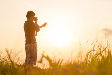 Young man is looking at sunset. Traveller with camera