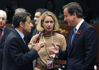 France's President Sarkozy talks to Britain's PM Cameron during an EU leaders summit at the EU Council in Brussels