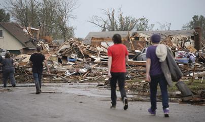 People walk through a neighborhood after a tornado struck Moore, Oklahoma