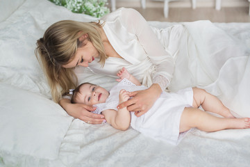 Happy young mother lies and plays with her little baby on a bed