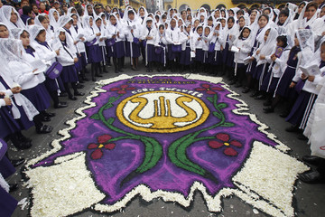 """Girls sing as they stand around a carpet of flowers during a procession to commemorate Peru's most revered Catholic religious icon, """"Lord of the Miracles"""", in Lima"""