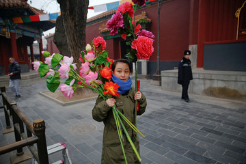 A woman holds flowers as people gather at Yonghegong Lama Temple to burn incense sticks and pray for good fortune on the first day of the Lunar New Year of the Rooster in Beijing