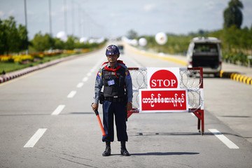 A policeman stands guard on the road leading to the ASEAN summit venue as security is tightened in Naypyitaw