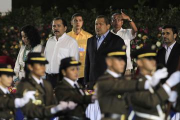 Nicaragua's President Ortega, Venezuela's President Chavez and Iran's President Ahmadinejad observe the honor guard during Ortega's swearing-in ceremony in Managua