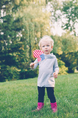 Happy adorable little blond Caucasian girl holding and waving American flag in park outside celebrating 4th july Independence Day Flag Day concept, action motion blur