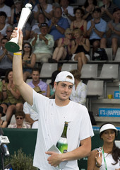 John Isner of the USA celebrates with the trophy after beating Arnaud Clement of France in their Auckland Open final  in Auckland