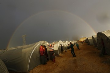 File photo of a Kurdish refugee from the Syrian town of Kobani showing victory sign as a rainbow forms over the camp in the southeastern town of Suruc