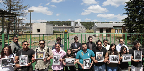 Participants of the European Meeting of Antiracist Leaders hold pictures in front of a pig farm, situated at the site of a former Roma concentration camp, to commemorate victims of the Holocaust in Lety