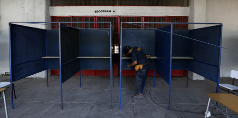 A worker arranges voting booths at the National Stadium which will be used as a voting station for the upcoming presidential elections in Santiago
