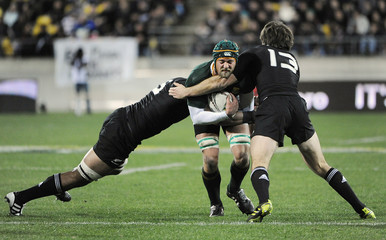 Kaino and Smith of New Zealand's All Blacks tackle Hargreaves of South Africa's Springboks during their Tri-Nations rugby union match in Wellington
