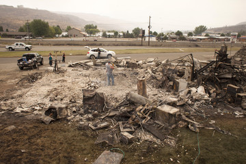 Josh Allen searches for belongings in the rubble of the building that contained his apartment with help from Ezra Crooks after it was completely destroyed by the Carlton Complex fire in Pateros