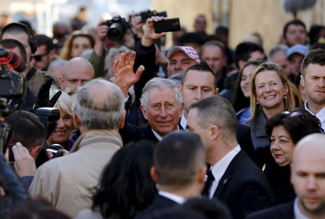 Britain's Prince Charles waves to people as he walks in Zagreb's down town