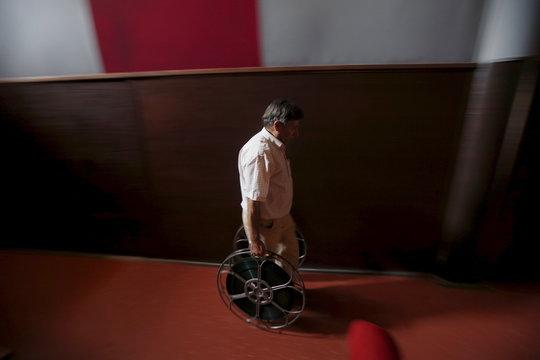 Projectionist Antonio Feliciano carries projection reels at Girasol cinema in Vila Nova de Milfontes