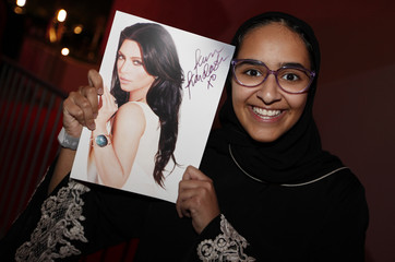 A Saudi fan holds a picture of U.S. television celebrity Kim Kardashian, for her autograph during her promotional visit to a newly built shopping mall in Riffa, south of Manama