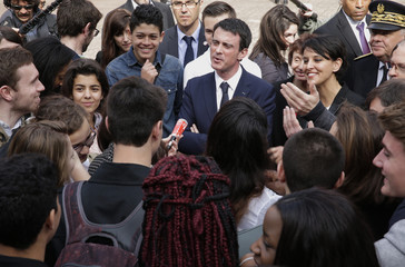 French Prime Minister Manuel Valls and Education and Research minister Najat Vallaud-Belkacem speak with students after a meeting at the Lycee Leon Blum high school in Creteil near Paris