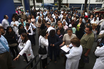 Employees wait outside a private hospital after an earthquake in Mexico City