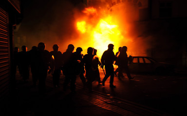 Riot police charge past burning buildings on a residential street in Croydon, south London