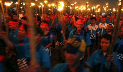 """Balinese Hindu worshippers walk with torches during a ritual ceremony to welcome """"Nyepi"""", Bali's Day of Silence and the Hindu New Year, at Monumen Nasional in Jakarta"""