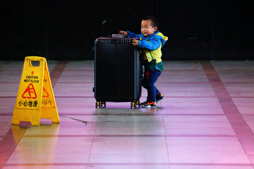 A boy pushes a suitcase at the departure hall of the Beijing Railway Station in central Beijing