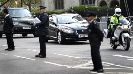 The limousine driving Britain's Prince Harry and Kate Middleton is escorted by police as they leave Westminster Abbey in London