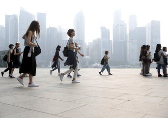 Tourists pass the central business district shrouded in haze in Singapore
