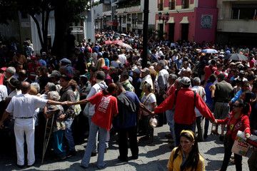 People wait to apply for a card that will register them for government social programmes, in Caracas