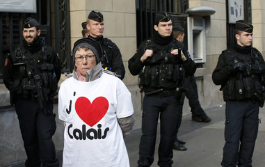A resident of Calais stands in front of French police during a protest urging the government to help their failing businesses and restore the image of their port city affected by the migrants crisis, in Paris