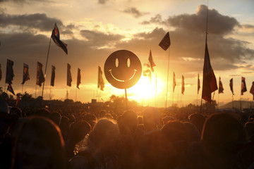 A festival-goer holds up a smiley face as the sun sets in front of the Other Stage at Worthy Farm in Somerset, during the Glastonbury Festival