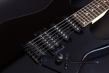 Black electric guitar close up on dark background.