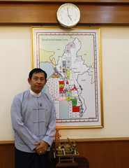 Myanmar's Energy Minister Than Htay poses for a picture in front of a map depicting Myanmar's energy resources in his office in Naypyitaw