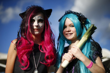 Attendees dressed as Hatsune Miku (R) and a cat person pose outside the MCM Comic Con at the Excel Centre in East London