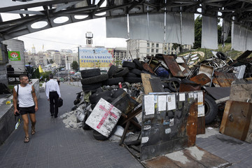 People walk past a barricade erected by protesters near Independence Square in central Kiev
