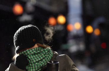 A woman covers her face to protect herself from the frigid cold temperatures though downtown Chicago