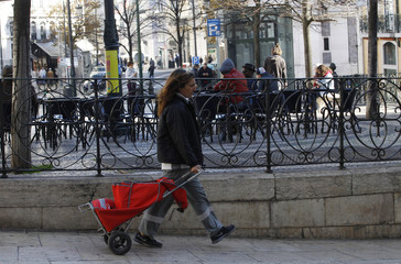 A postwoman walks with her mail bag as she delivers mail in Lisbon
