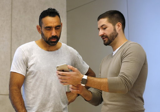 AFL football player Goodes is assisted by an Apple employee in setting up his Apple Watch at the company's flagship store in Sydney