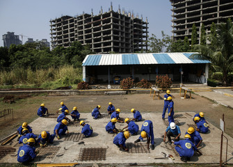 Students tie iron bars at an outdoor classroom at the Larsen & Toubro construction skills training institute in Panvel