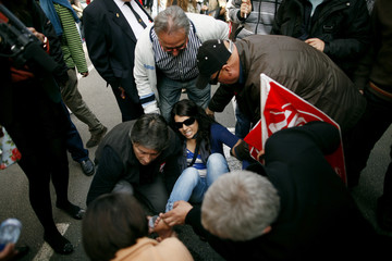 SUR Tv Journalist Rossel Aparicio is helped by demonstrators after she was injured by a firecracker during a nationwide general strike in Malaga