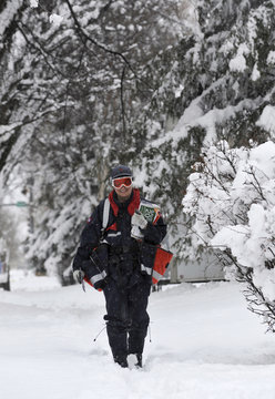 A Canada Post letter carrier trudges through the snow during a heavy spring snowfall that blanketed the Edmonton region