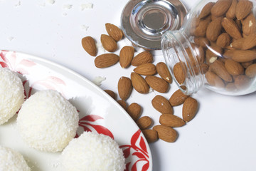 Preparation of Raffaello sweets at home. Ready-made sweets lie on a plate. On a background of a jar with scattered almonds.