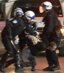 A man is detained during a protest against student tuition hikes in Montreal