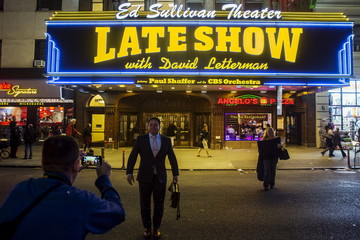 """Fans take photographs of each other with the marquee for """"The Late Show"""" with David Letterman outside of the Ed Sullivan Theater in Manhattan during taping of the final edition of the show in New York"""