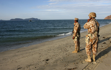 Soldiers stand on the shore of Punta Bufeo