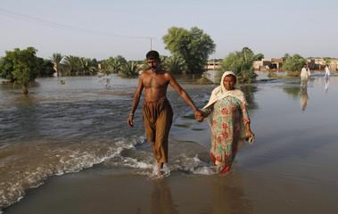 Flood victims wade through a flooded area in Muzaffargarh, Punjab province