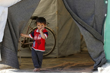 A Syrian refugee boy stands in front of his family's tent in Al Zaatari refugee camp, in the Jordanian city of Mafraq, near the border with Syria