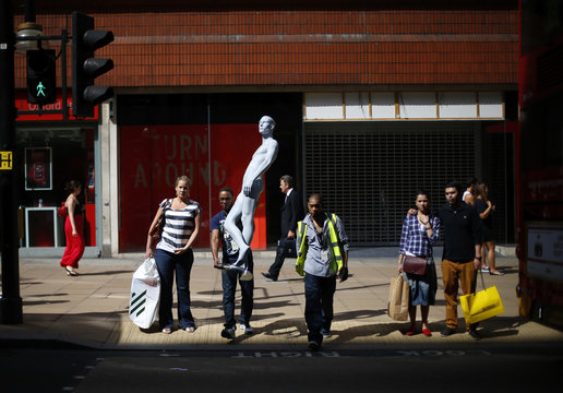 Shoppers wait to cross the road next to a man carrying a shop window mannequin on Oxford Street in London