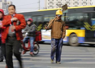 A worker carrying a shovel crosses a street in Beijing