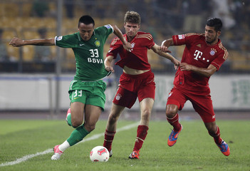 Bayern Munich's Mueller and Can fight for the ball against Beijing Guo'an's Mao during a pre-season friendly soccer match in Beijing