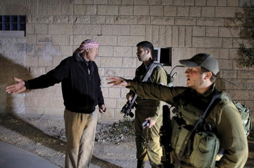 Palestinian man speaks with Israeli soldiers as they search for a missing Israeli near the West Bank city of Hebron