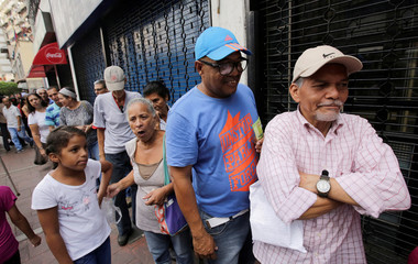 People wait for their turn to buy bread at a bakery in Caracas, Venezuela