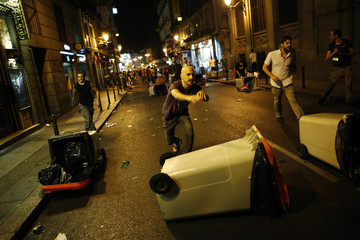 Demonstrators throw garbage containers onto the ground during clashes after a protest against government austerity measures in central Madrid